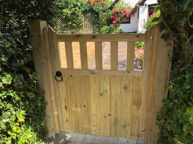 wooden garden gate in between two bushes
